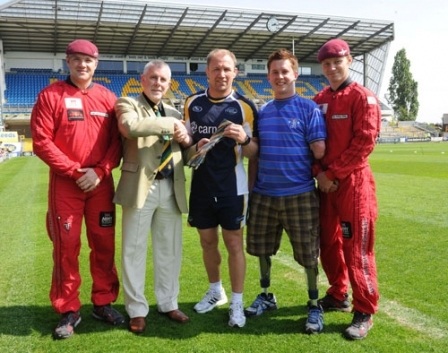 Nigel Morgan, Operations Manager of the Yorkshire Agricultural Society (centre) presenting a YAS tie to Neil Back, with Lance Corp Tom Neathway and flanked by members of The Red Devils